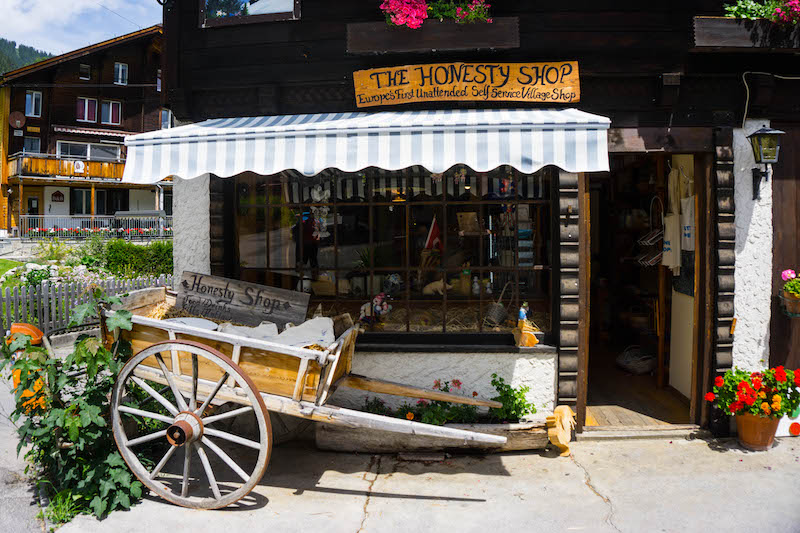 [storefront with wheelbarrow reading 'the honesty shop'] in Gimmelwald, one of the best places to visit in Switerland