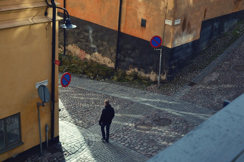 A man walking on a cobbled street. Sodermalm neighborhood is home to some of the best hostels in Sweden.