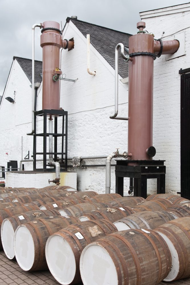 White distillery building with whiskey barrels outside