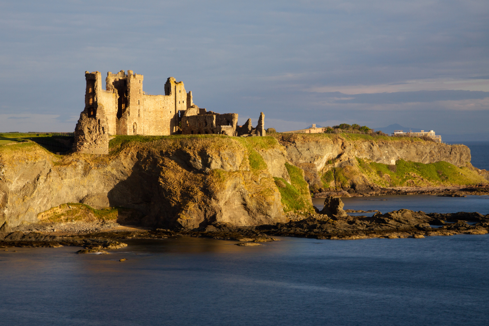 Cliffside castle on a rugged coastline and water