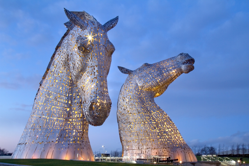 Two giant horse head sculptures lit up at night
