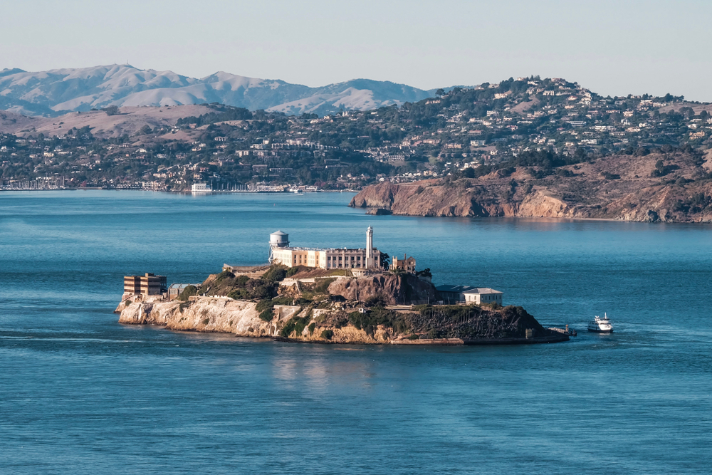 A small island, Alcatraz, with an abandoned prison building on it, in the middle of beautiful turquoise water surrounded by a city.