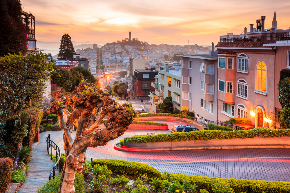 A view of the crooked turns of Lombard Street, lit up at night with a light trail from a car, with a view of Coit Tower off in the distance.