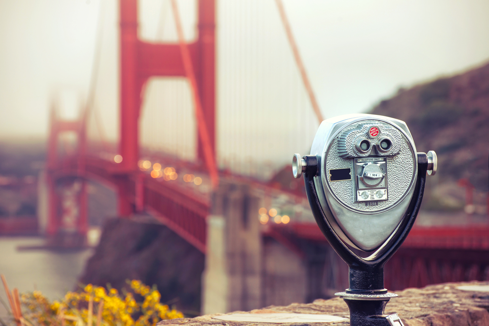 Pay-per-use viewfinder in focus with an out of focus background of the Golden Gate Bridge with cars on it on a foggy day.