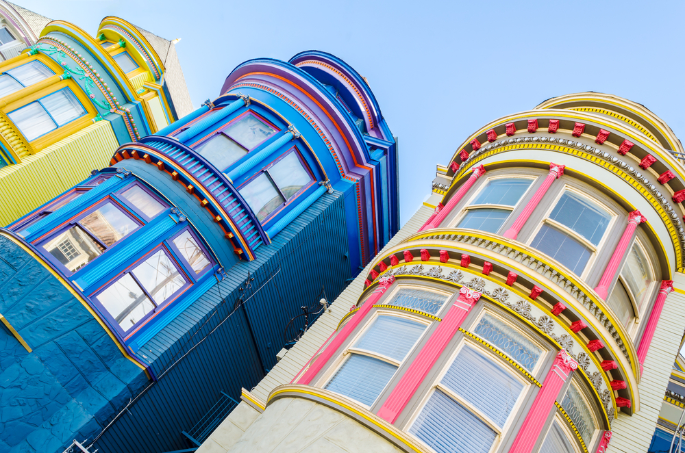 View from a low angle of the rounded, colorful, detailed buildings of San Francisco architecture: one yellow, one blue, and one pink-and-white building.
