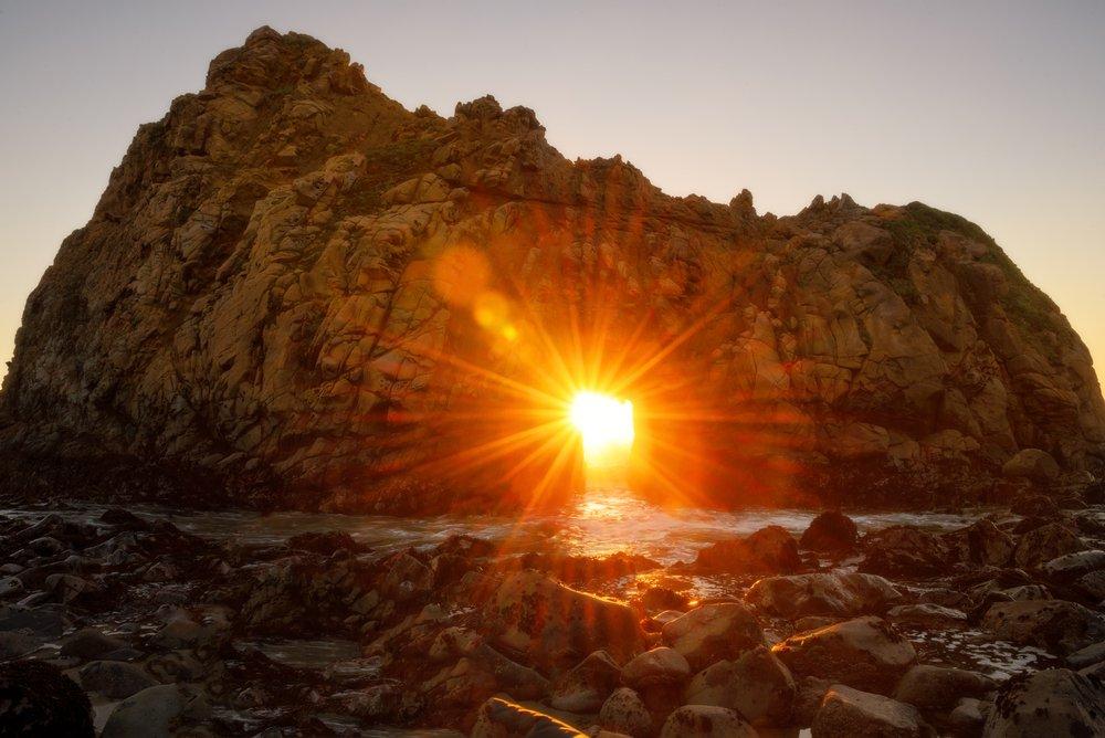 sun burst going through the keyhole arch at pfeiffer beach
