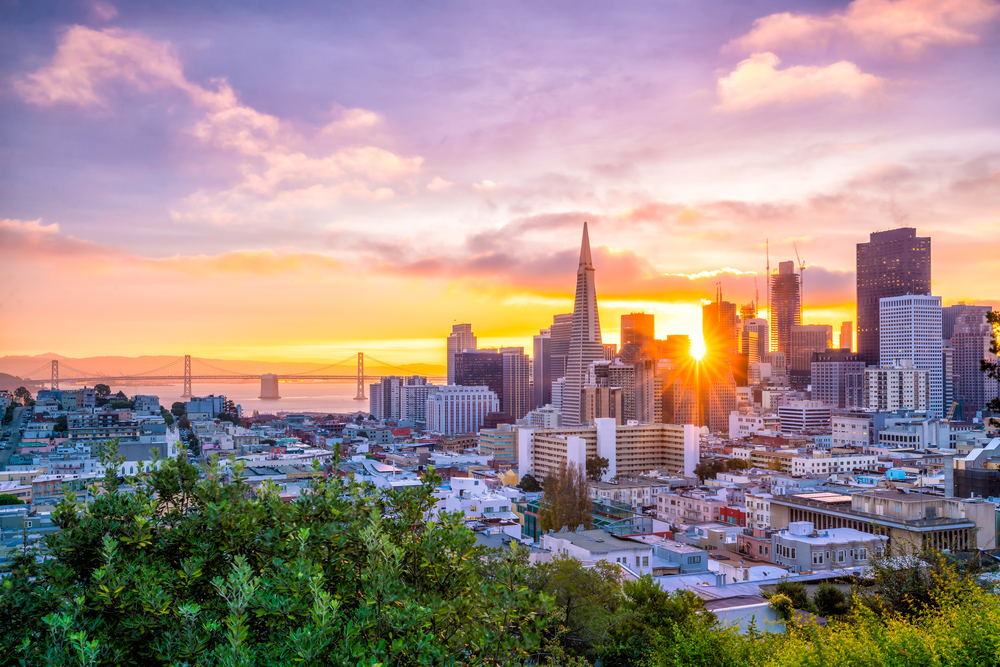 A view of the San Francisco skyline from up on a hill with greenery in the foreground and a sunburst seen through the skyline at sunset, a view of a bridge in the distance.