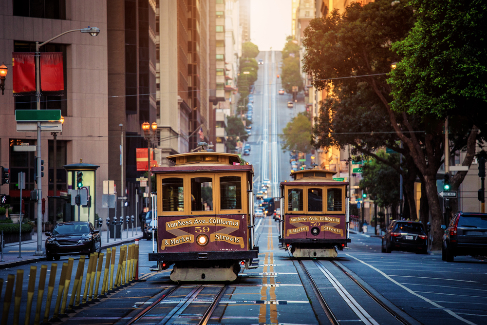 Two distinctive San Francisco red-and-gold cable cars passing each other on a busy city street with soft afternoon light.