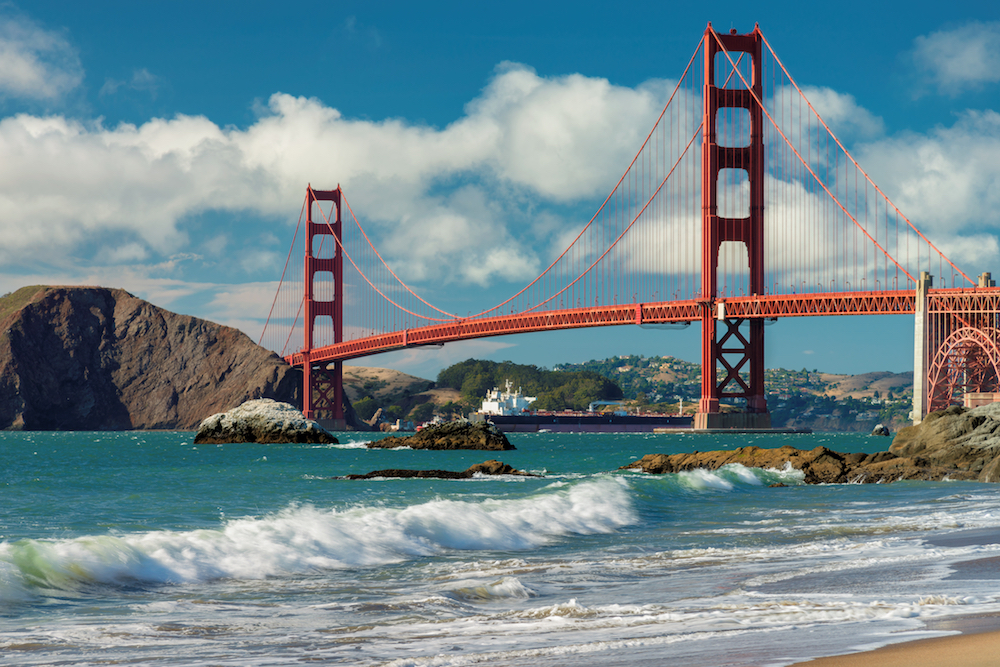 View of waves crashing on the beach with a view of the red suspension bridge, the Golden Gate Bridge, over turquoise water on a partly cloudy day.
