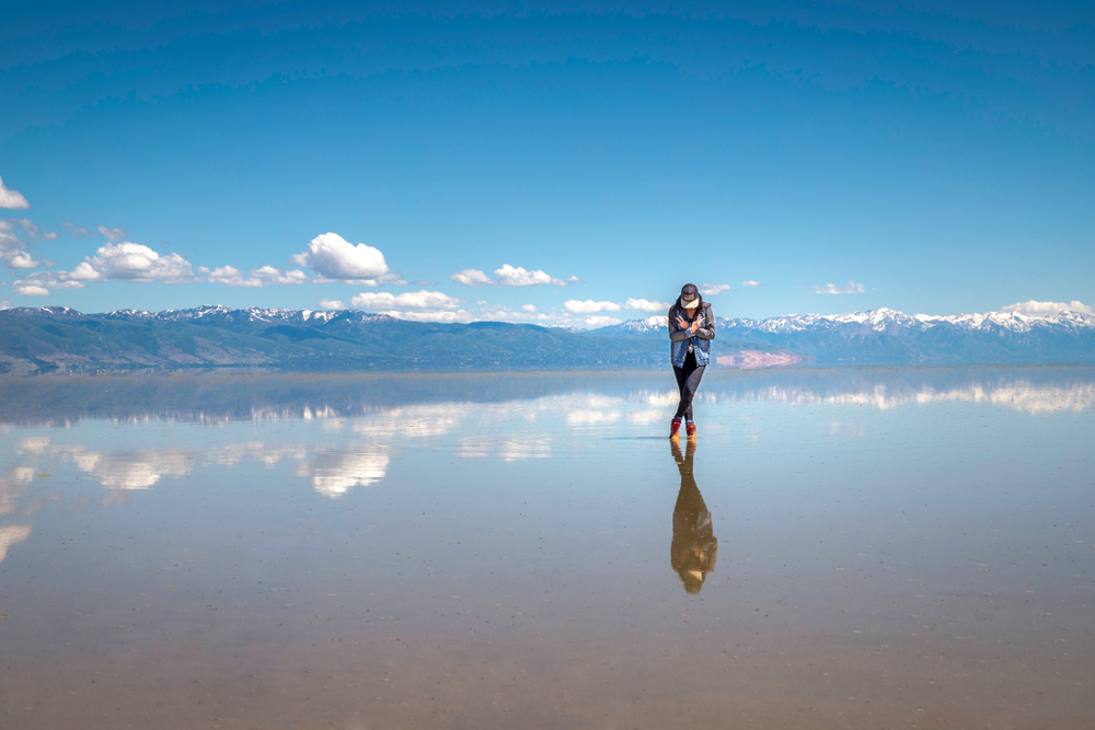 Woman standing on reflective salt lake with shallow water and clouds