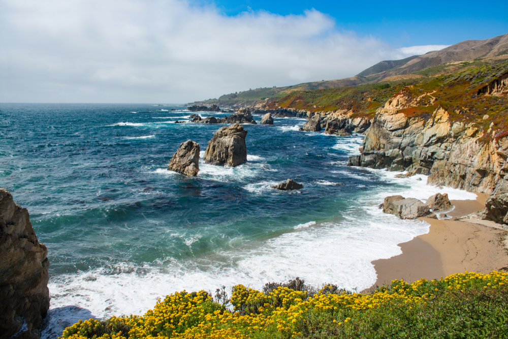 the sandy shore and blue ocean waters of the rugged garrapata beach with rock outcroppings in the water