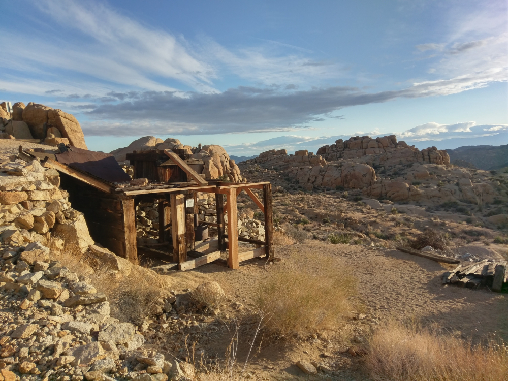 A view of an abandoned gold mine held up by planks in the rocky desert atmosphere of Joshua Tree National Park