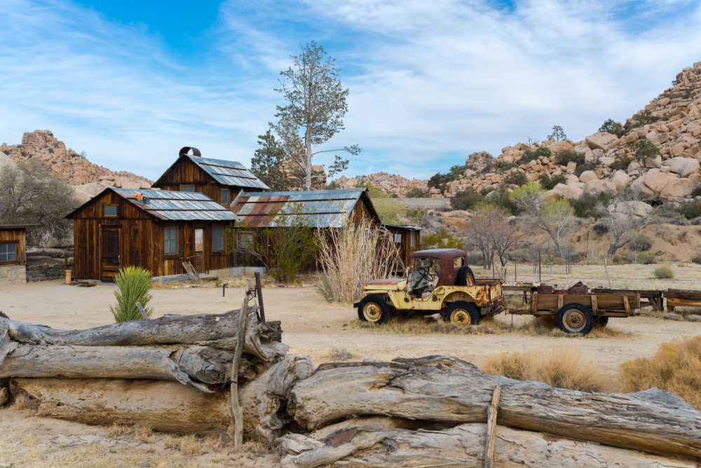 A broken down car and the remnants of a ranch (wooden house with tin roof) in the middle of Joshua Tree's desert landscape on a partly cloudy day.