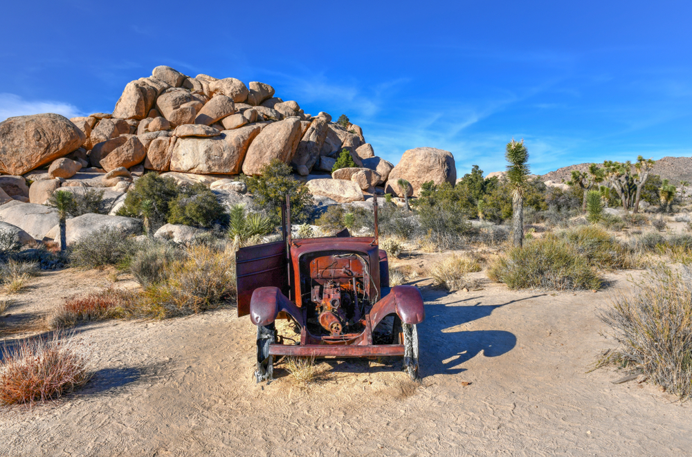 A broken down, rusted over red car in the middle of a Joshua Tree landscape.