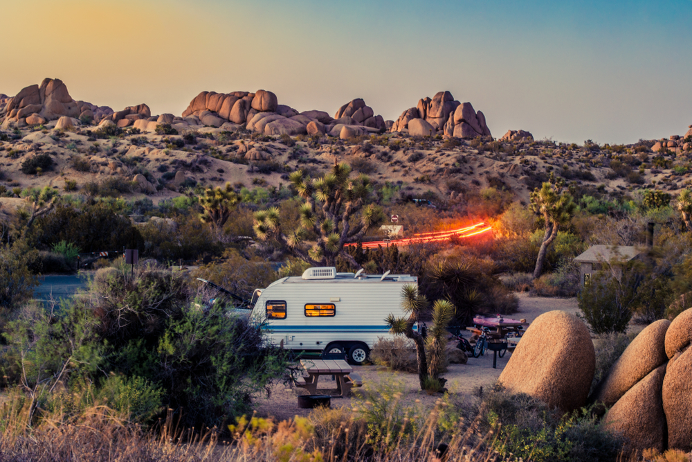An occupied RV with the lights on in the landscape of Joshua National Park with some light trails in the background from a moving car near sunset.