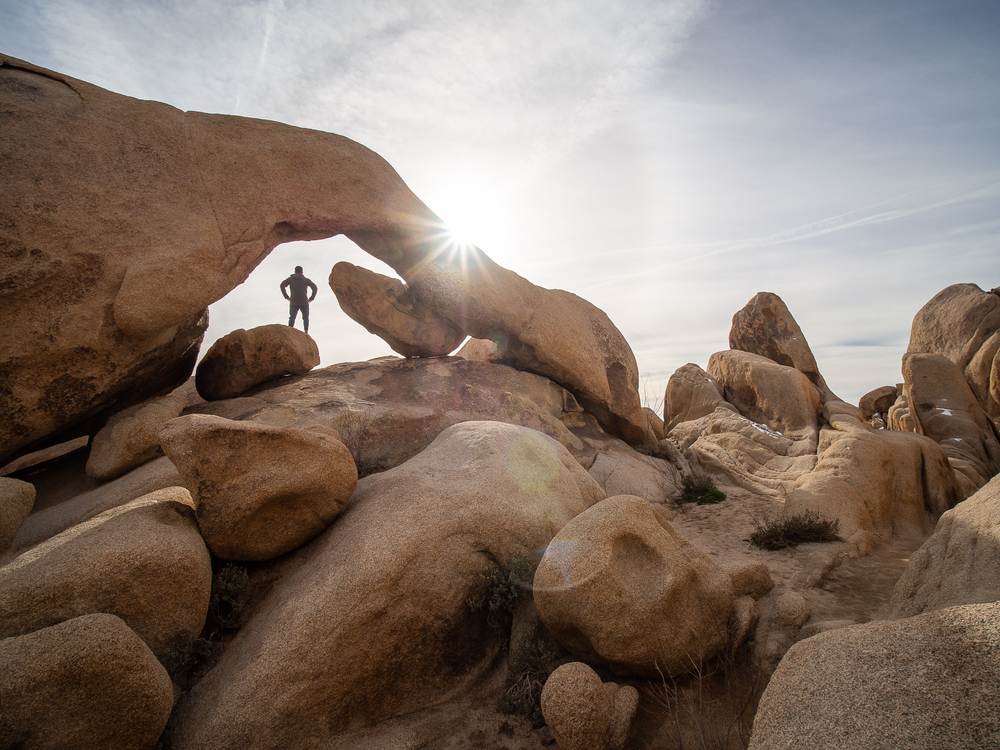 A man standing underneath a rock arch with a foreground of lots of smooth rocky boulders on a partly cloudy day, with a sunburst hitting the rock arch.