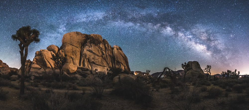 A panoramic view of the rocks and trees of Joshua Tree National Park with the milky way lit up overhead in colors of lavender, pink, and blue.