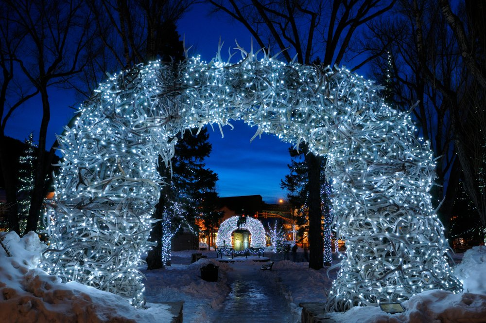 "The famous ""antler arch"" in Jackson in winter styling with lots of blueish Christmas lights on it, making it shine a pale blue color"