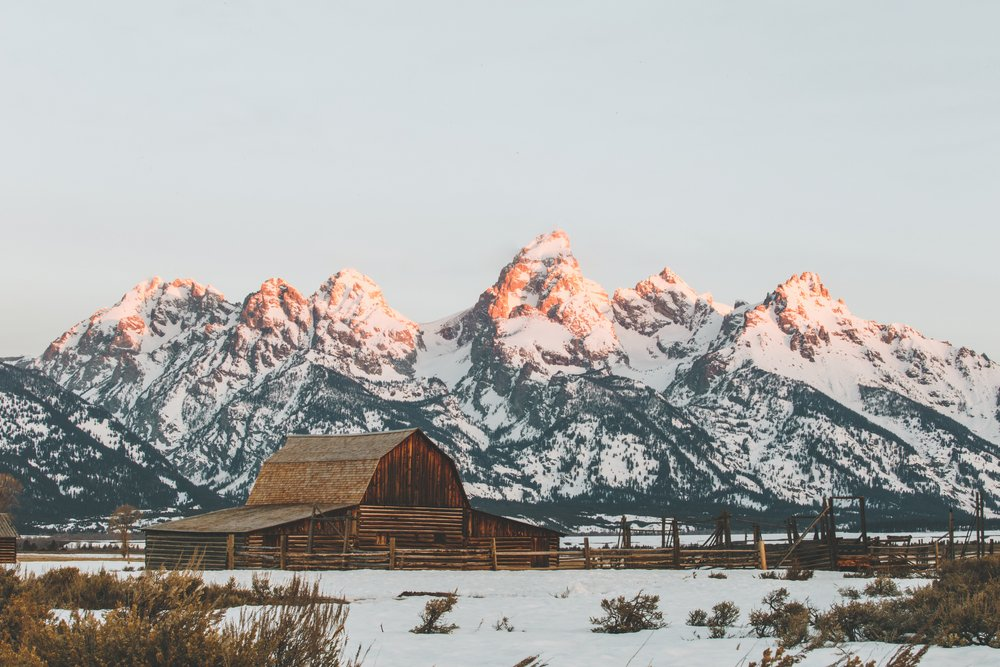 A famous barn in Grand Teton in the winter with snow covered mountains with alpenglow (sunlight on the mountain peaks) in background