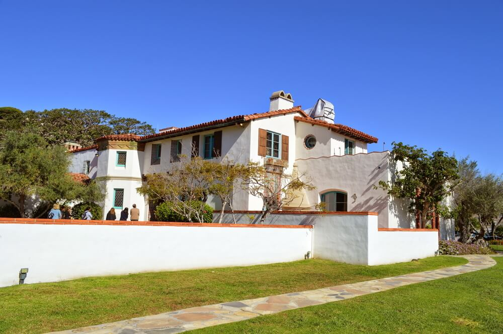 White stucco-style house with lots of Spanish colonial style architectural detailing on a sunny day on a Malibu California day trip