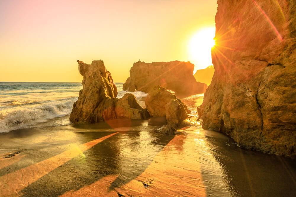 Sunset falling over the Pacific at El Matador Beach in Malibu bathing the water and beach in a beautiful orange glow at sunset, finishing the perfect day in Malibu
