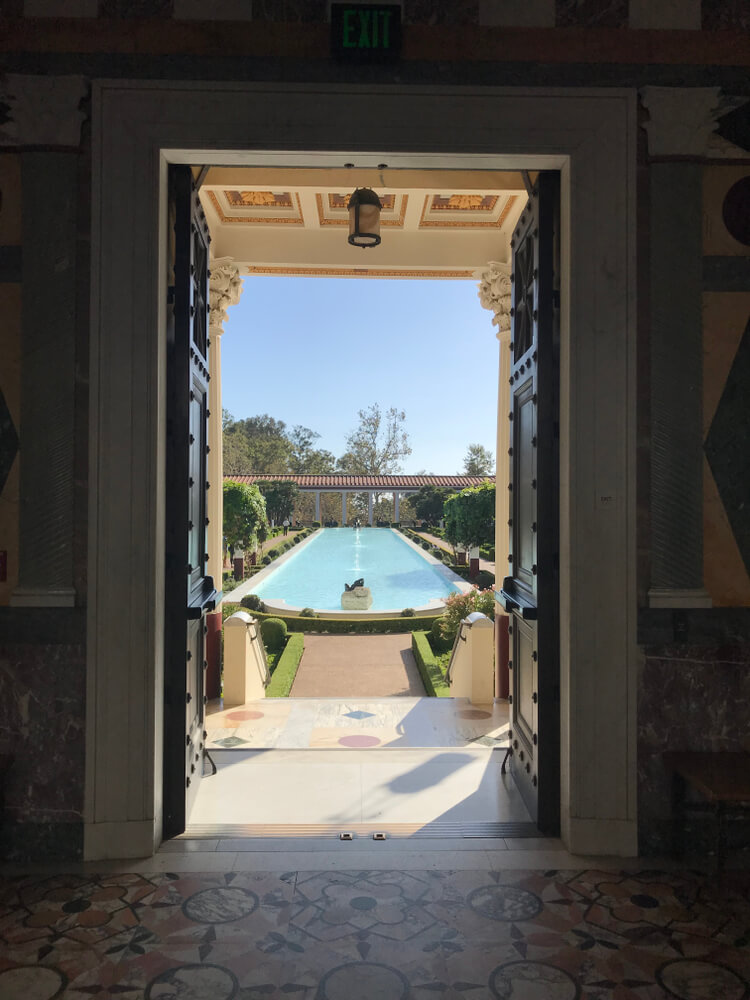 Vertical photo showing the pool of the Getty Villa as seen through an open door