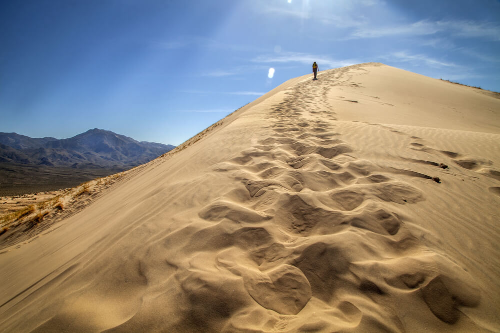 trail of footprints left in the sand as a single hiker ascends the sand dune