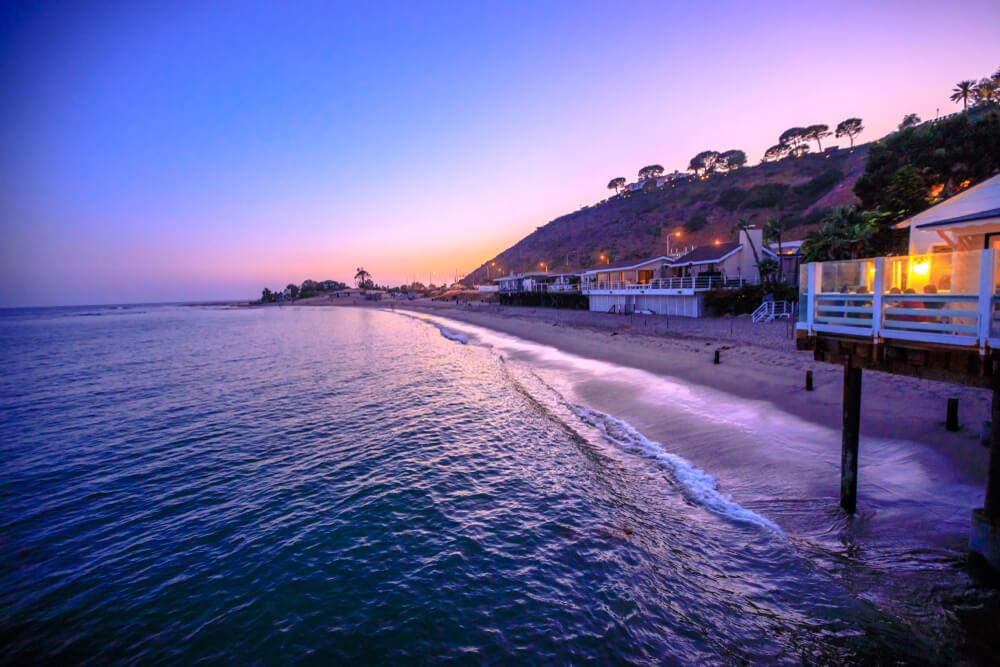 Scenic coastal landscape with Santa Monica Mountains and Surfrider Beach at dusk illuminated by night.