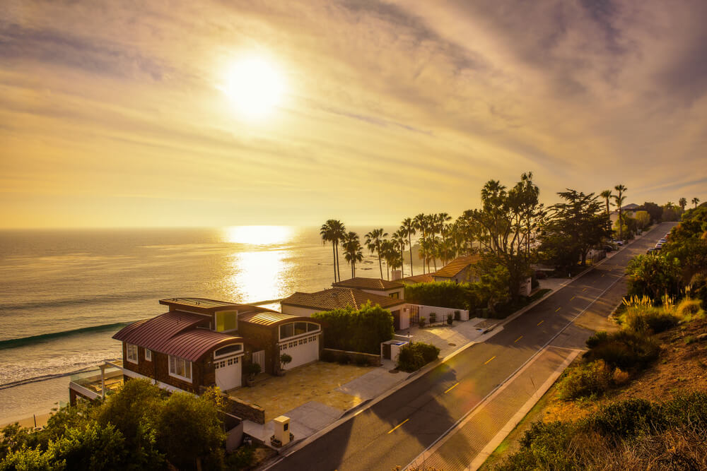 Sun setting over the coastline of Malibu with the pacific coast highway and beach being bathed in golden light on a Malibu day trip.