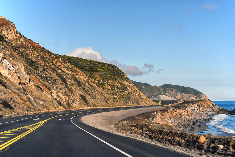 view of the pacific coast highway winding through malibu, driving to malibu for a day trip from LA