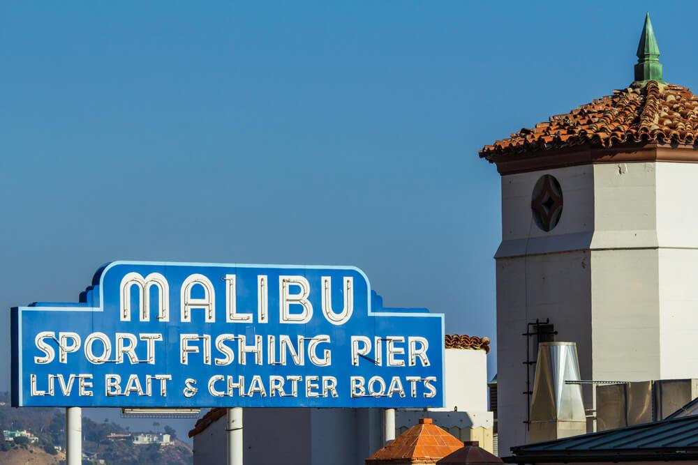 "Iconic sign marking the Malibu Pier, along the Pacific Coast Highway in southern California. ""Malibu sport fishing pier, live bait & charter boats""."