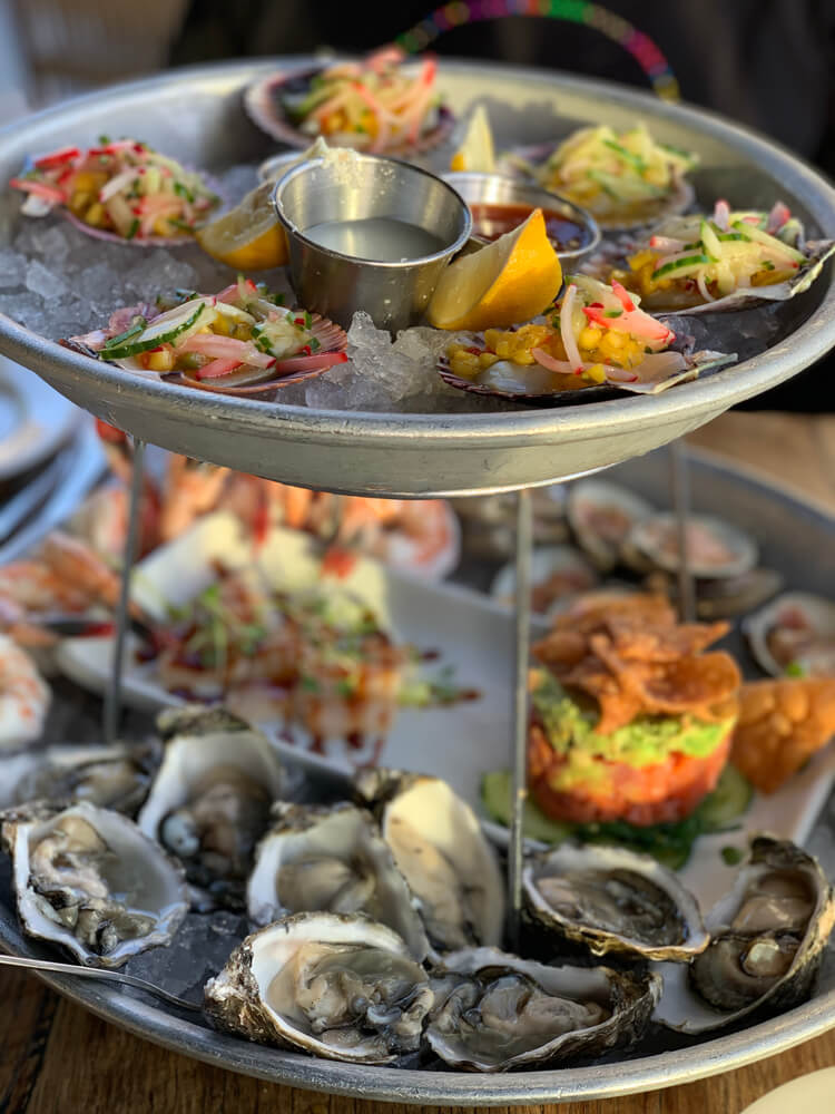Platter full of fresh seafood including oysters, clams with a salsa on top, and poke
